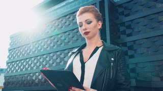 Sexy business woman with tablet. Red-haired girl.