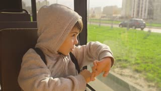 The boy is riding in the bus looking out the window