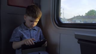 The boy is riding in the train, playing games on the tablet