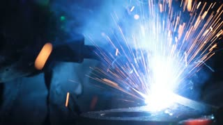 Welding on an industrial plant. Industrial Robot arm active in factory. Automation welding mechanical procedure. Close up