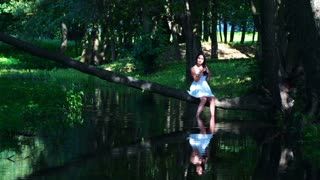 Young brunette girl posing near the water, sitting on a fallen tree