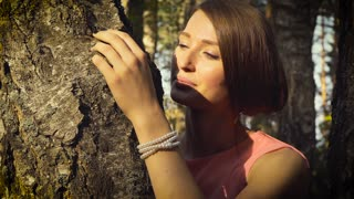 Young girl among forest trees