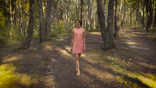 Young girl in a pink dress is walking in the woods