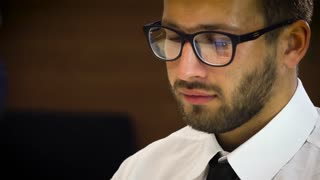 Young male businessman in a white shirt and glasses, working at a computer in the office