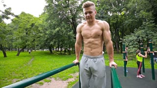 Young man in good physical shape, is engaged on the bars