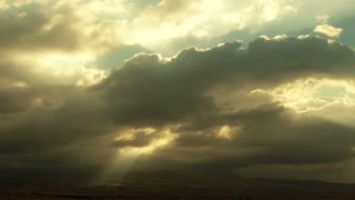 Clouds 1301: Beams of sunlight shoot through time lapse storm clouds and light the ground.