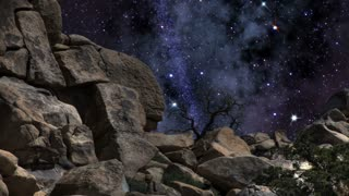 The Heavens 0303: A midnight starry sky turns above giant rock formations.