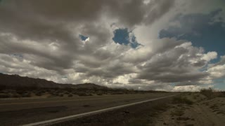 Time Lapse 2032: Time lapse storm clouds travel over an old road in the Mojave Desert, California, USA.
