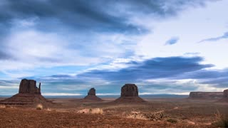 Time lapse clouds travel over Monument Valley National Monument as night falls.