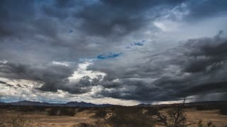 Time lapse storm clouds and lightning over a desert plain.