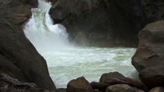 Waterfall 0309: A waterfall gushes through big rocks into a pool (Loop).