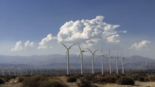 Wind Power 0212: Hundreds of speedy windmills under time lapse desert clouds.