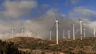 Wind Turbine 3006: Wind turbines turn against time lapse clouds.