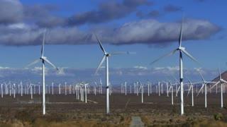 Wind Turbine 3010: Wind turbines turn against time lapse clouds.