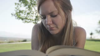 close up of girl reading book in park