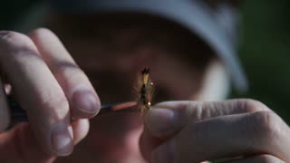 close up of man prepping fishing fly