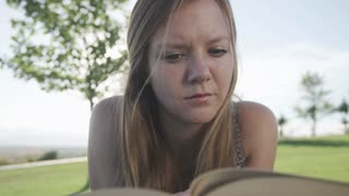 close up of woman reading book in park