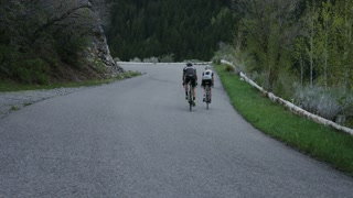 Couple road biking through mountains