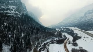 drone shot following river through snowy mountains