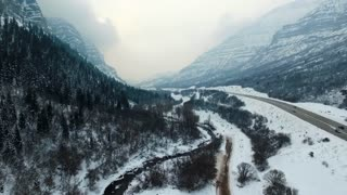 drone shot of road going through snow covered mountains