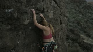 girl reaches for hold while rock climbing
