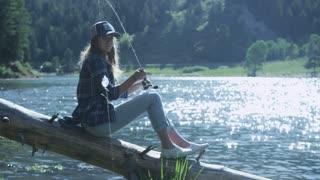 girl sitting on a log fishing