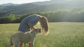 girl standing in field petting her dog