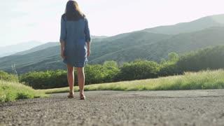 girl walking down dirt road next to field