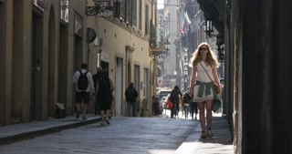 Girl walking down street in Italy, pauses to look around the cobblestone alleyway