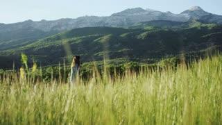 girl walking through field of tall grass