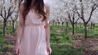 girl walking toward camera through white blossoms in orchard