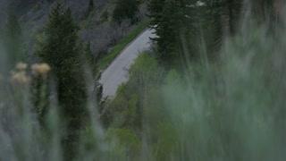 Man road biking up hill through mountains