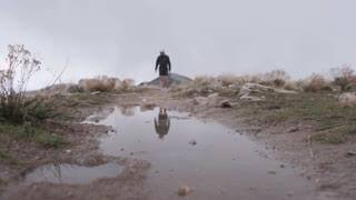 man runs over puddle