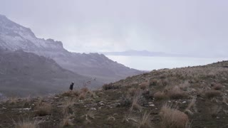 man runs uphill on trail through storm