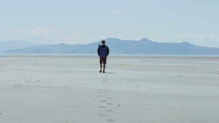 Man walks out onto cold beach