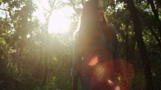 panning shot of girl walking through trees