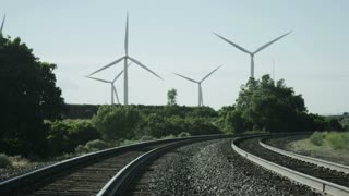 panning shot of windmills blowing in background of railroad tracks