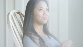 Pregnant asian woman in rocking chair holding belly