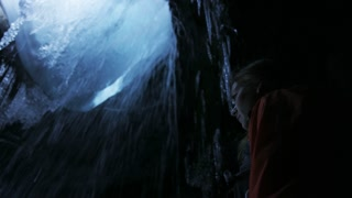 slow motion girl admiring waterfall in frozen cave