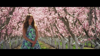 Slow motion girl in pink orchard looking at camera