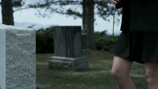 slow motion girl leaving rose on grave stone in cemetary