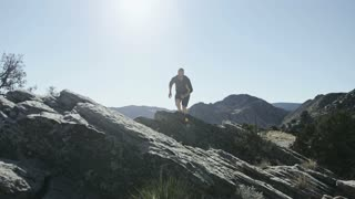 slow motion man trail running jumps off of rock