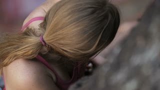slow motion of girl clipping rope while rock climbing