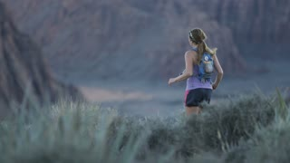 slow motion of girl trail running in desert