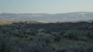 slow motion of girl trail running in desert