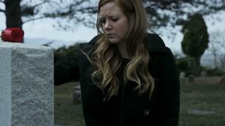 slow motion somber girl leaving rose on grave stone in cemetery