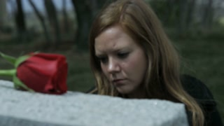 slow motion somber girl visiting grave stone in cemetery