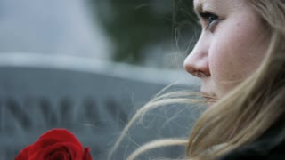 slow motion somber girl with rose visits gravestone in cemetery