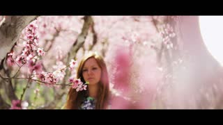 slow motion woman stares intensely at camera in pink blossom orchard