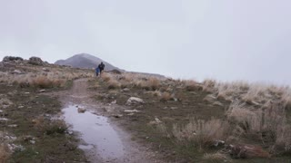 two men run on trail while snow falls on Antelope Island, Utah